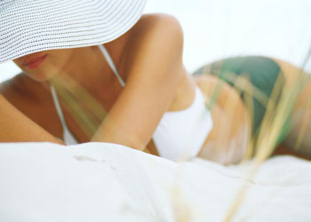 Woman wearing white hat lying at the beach