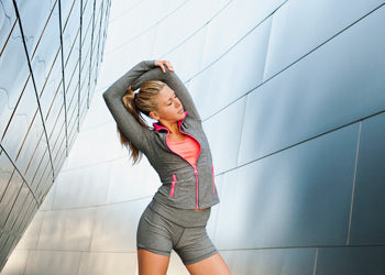 blond woman stretching herself in front of buildings