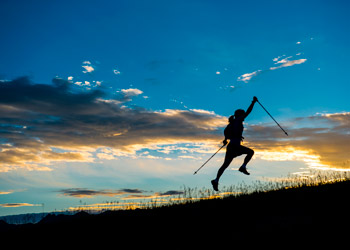 female silhouette jumping while hiking on a mountain by sunset