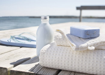 White towels with bodylotion and purple soap lying outside at wellness center