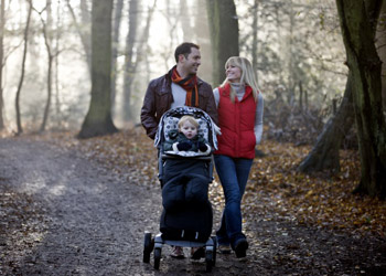Young family taking a walk in nature with their baby in fall