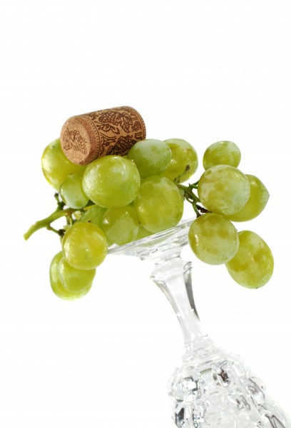 wineglass with grapes and corks