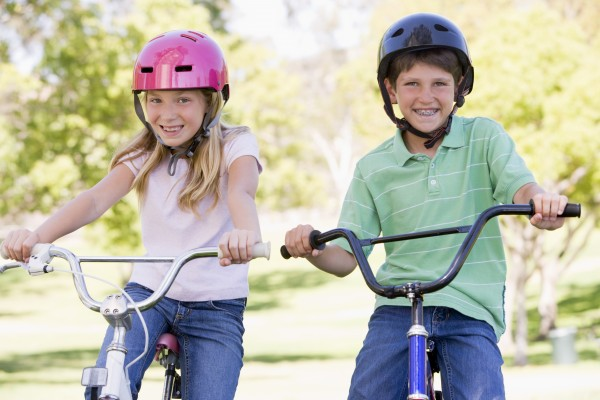 brother and sister outdoors on bicycles