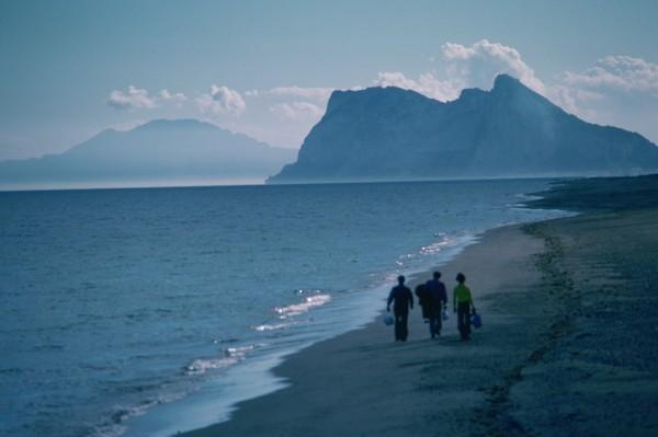 three people walking on the beach