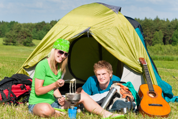 young camping couple cooking meal outside