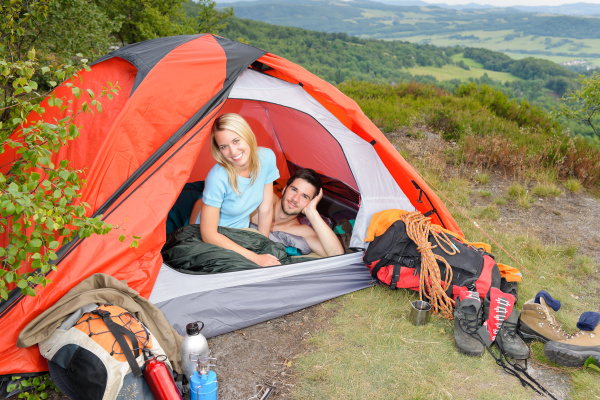 camping young couple sunset tent climbing