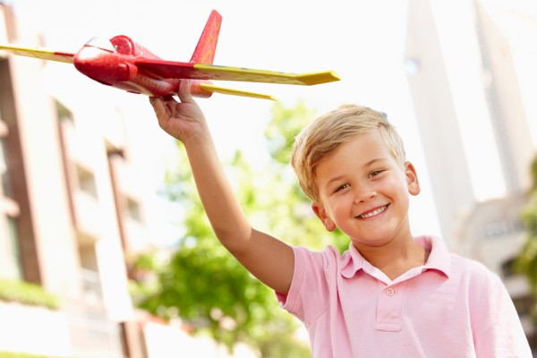 young boy outside with toy aeroplane
