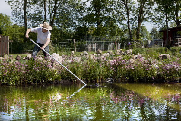 gardener with straw hat cleansing pond