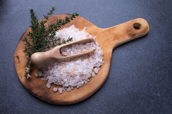 salt with measuring spoon on round
