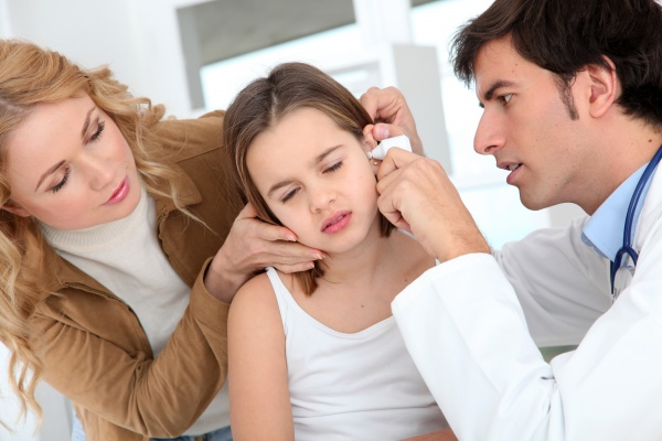 doctor looking at little girl ear