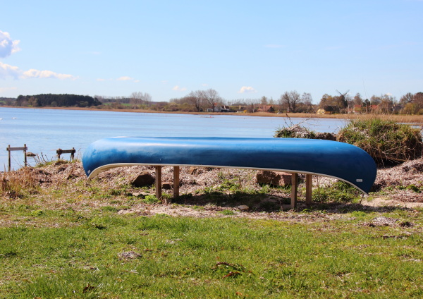 canoe placed at beach with blue