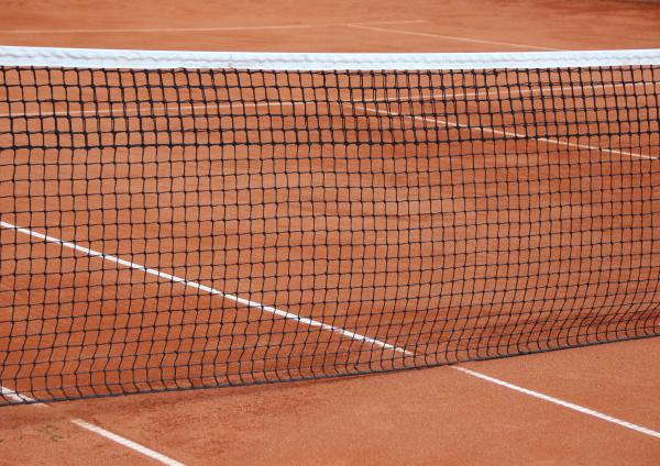 tennis net at empty red gravel
