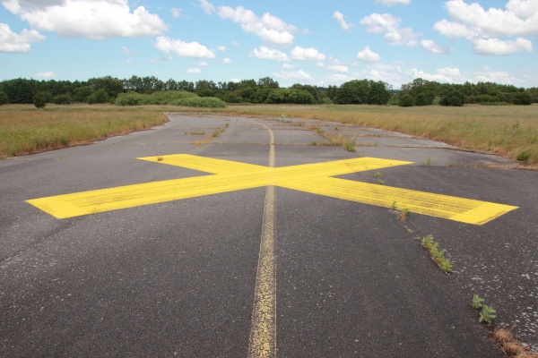 yellow painted cross on asphalt with