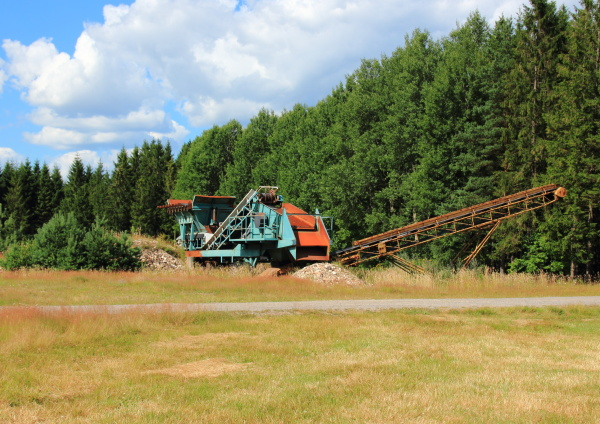 gravel machine in forest with sky