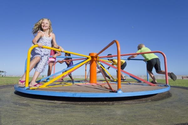 smiling children riding carousel in park