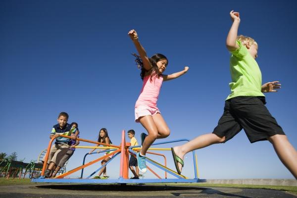 children jumping off merry go round
