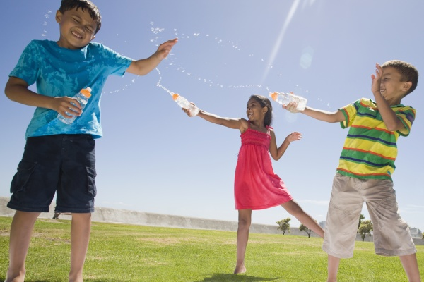 children squirting water at each other