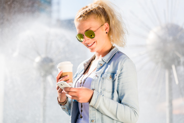 woman with phone and coffee at