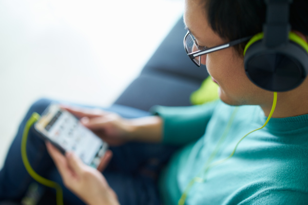 asian man with green headphones listens