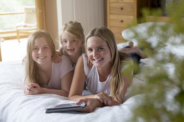 three sisters using a digital tablet