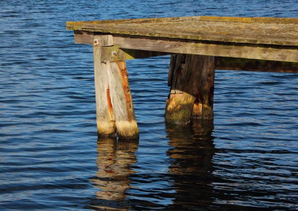 wooden pier end with dark water