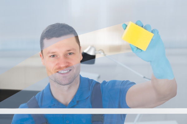 worker cleaning glass with rag