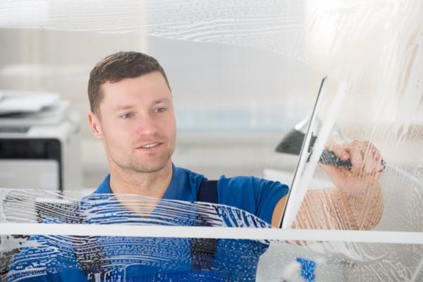 worker cleaning soap sud on window