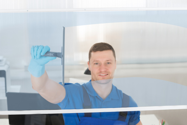 worker cleaning glass window with squeegee