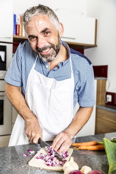 austria man in kitchen chopping onions