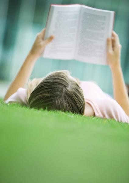 teenage girl lying in grass reading