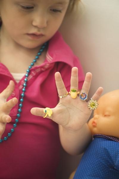 little girl wearing plastic rings on