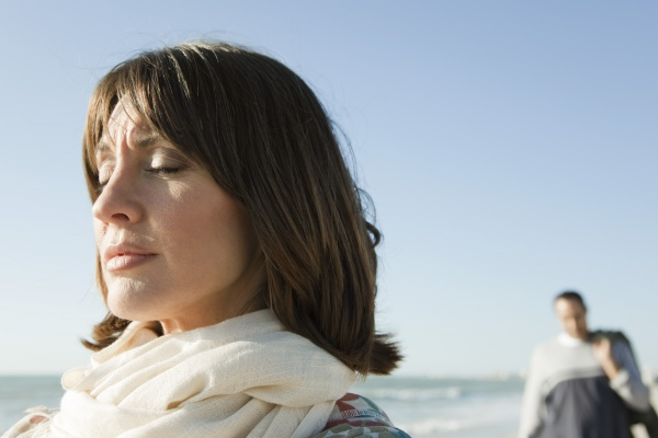 woman standing on beach with eyes