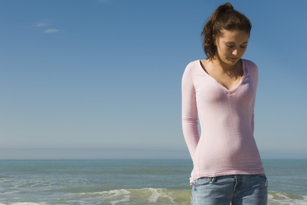 preteen girl on beach contemplatively looking