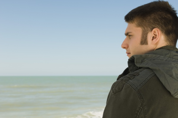 young man at beach contemplatively looking