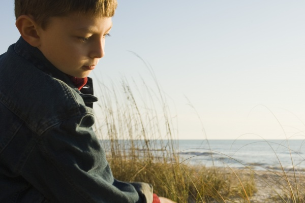 young boy outdoors contemplatively looking away
