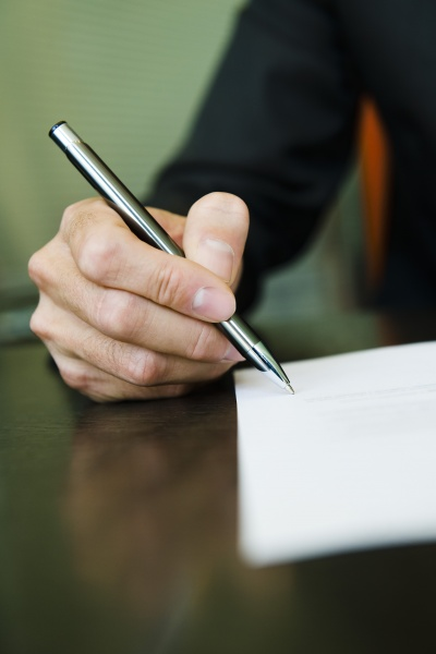 person signing paperwork cropped