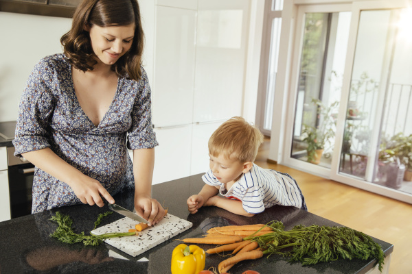 pregnant woman cutting vegetables with her