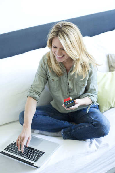 smiling blond woman with laptop using