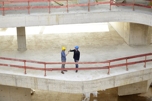 two men with hard hats clinking