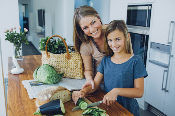 mother and daughter in kitchen slicing