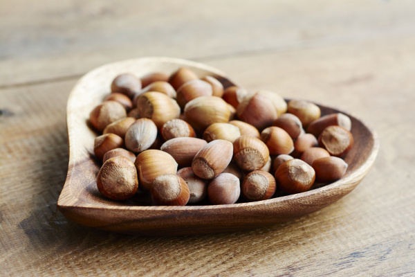 hazelnuts in a heart shaped wooden