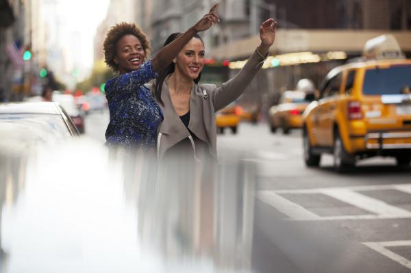 women hailing taxi on city street