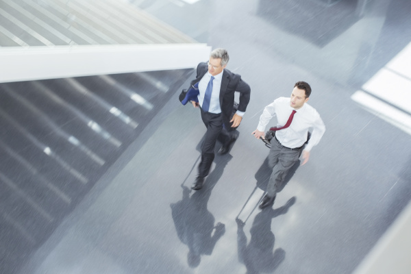 businessmen with suitcases running in lobby
