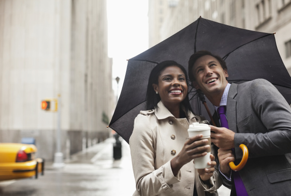 business people holding umbrella on city