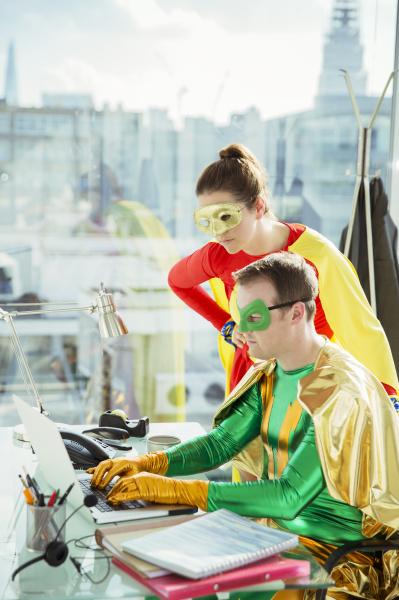 superheroes working on laptop in office