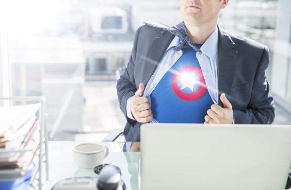 businessman opening shirt to reveal superhero