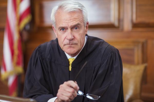 judge sitting behind judges bench in