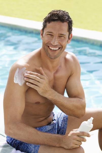 man applying sunscreen by swimming pool