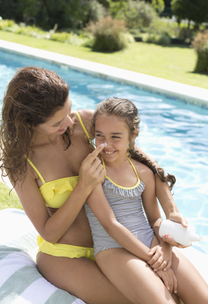 mother applying sunscreen to daughters nose