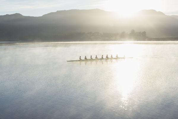 rowing team rowing boat on still